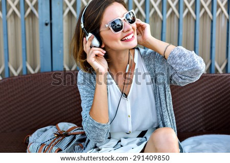 Young pretty woman sitting in the beach wearing stylish casual vintage styled outfit, relaxed and listening music, bright sunny colors, joy, amazing weekends. - stock photo