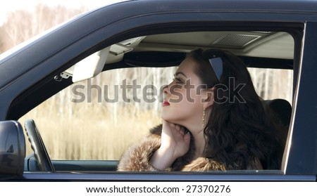 young pretty woman sitting in the car - stock photo