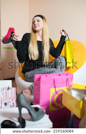 Young pretty woman sitting on a chair and holding women's shoes. Woman on the shopping