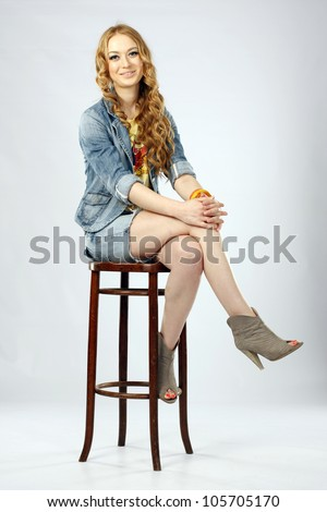 Young pretty woman sitting on a stool in studio