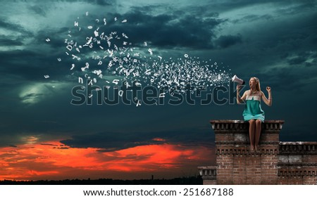 Young pretty woman sitting on building top and announcing - stock photo