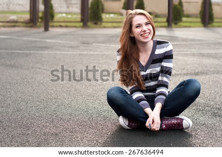 Young pretty woman sitting on the basketball court  - stock photo