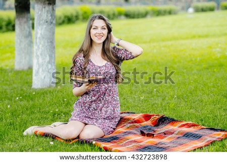 Young pretty woman sitting on the meadow and reading book outdoors in the park