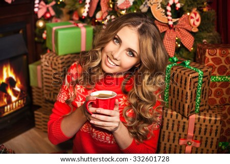 young pretty woman smiles and holding a cup with christmas tree on background - stock photo