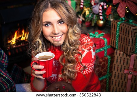 young pretty woman smiles and holding a cup with christmas tree on background