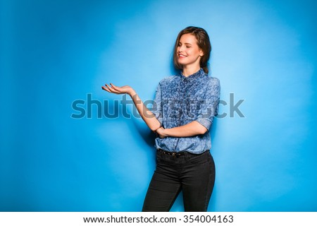 young pretty woman smilig in blue shirt standing on blue background, showing one side