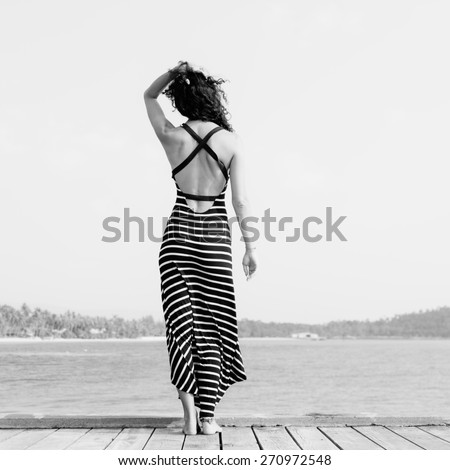 Young pretty woman standing alone on the pier near the sea and looking on the water and waiting for somebody in ocean - stock photo