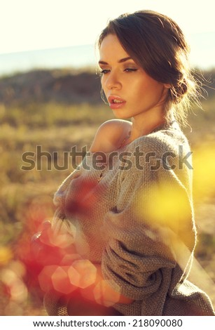 young pretty woman standing in autumn yellow colours field and dreaming with closed eyes. beautiful portraits made with backlit - stock photo