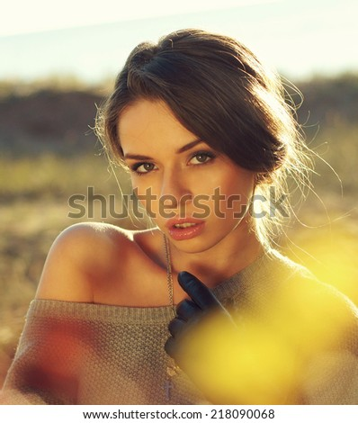 young pretty woman standing in autumn yellow colours field and looking at you charming. beautiful portraits made with backlit - stock photo