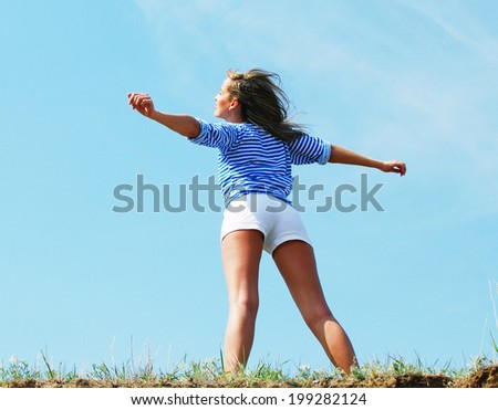 young pretty woman standing on the rock - stock photo