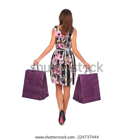 young pretty woman standing with color-full shopping bags, studio - stock photo