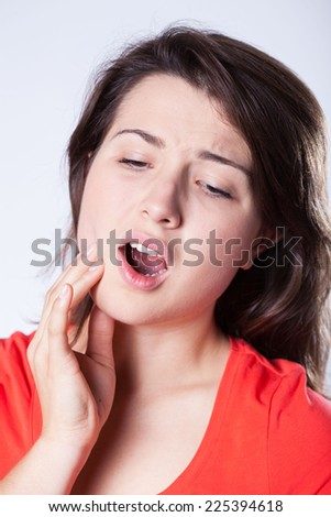 Young pretty woman suffering for toothache - stock photo