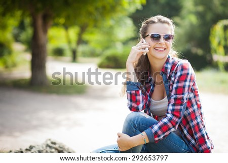 Young pretty woman talking on mobile phone profile, in autumn park