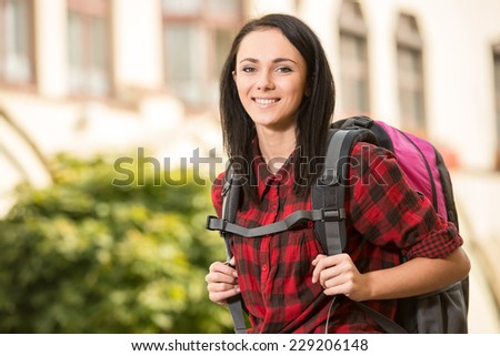 Young pretty woman, tourist with backpack, smiling. - stock photo