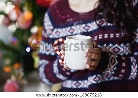 young pretty woman under new year tree with christmas cup of tea - stock photo