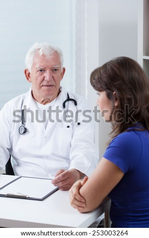 Young pretty woman visiting her older experienced physician