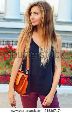 Young pretty woman walking alone at nice sunny day, white city background. Have long trendy blonde ombre hairs, - stock photo