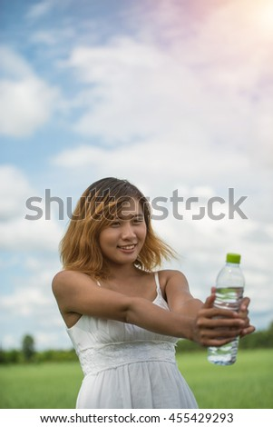 young pretty woman wearing white dress holding bottle of water at grassland smiley to camera look so fresh enjoy and happy.