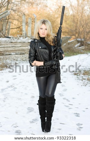 Young pretty woman with a gun outdoors - stock photo