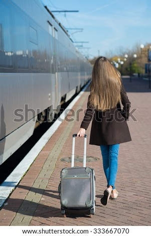 Young pretty woman with a suitcase on the train station in sunny day