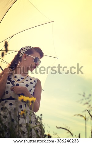 young pretty woman with a vintage rockabilly outfit and a sunshade in a meadow, backlight