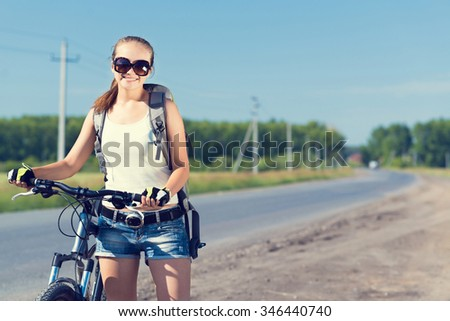 Young pretty woman with backpack riding bicycle outdoors