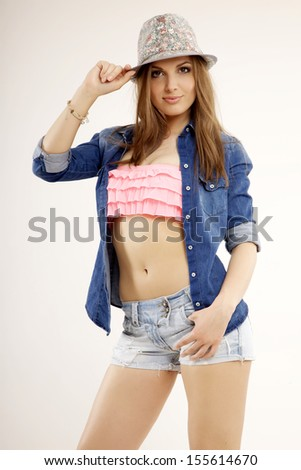 Young pretty woman with beautiful blond hairs and multicolor makeup and blue jeans dress short and shirt in the hat isolated on white background - stock photo