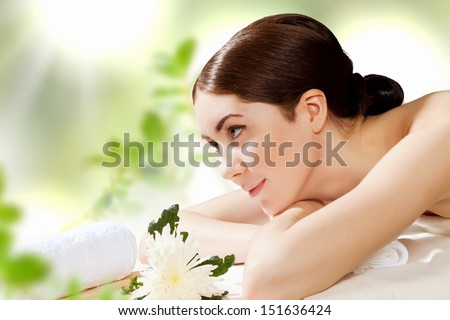 Young pretty woman with clear skin at spa salon getting massage