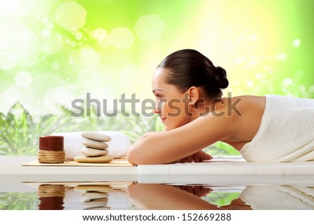 Young pretty woman with clear skin at spa salon getting massage - stock photo