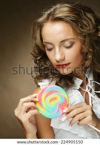 Young pretty woman with colorful lollipop  - stock photo