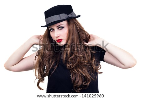 Young pretty woman with hands in hair and black hat. White background