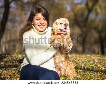 Young pretty woman with her dog American Cocker Spaniel sitting in city park in sun lights in autumn