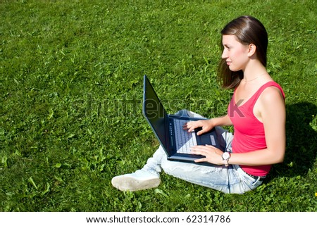 Young pretty woman with laptop sitting on green lawn in a park - stock photo