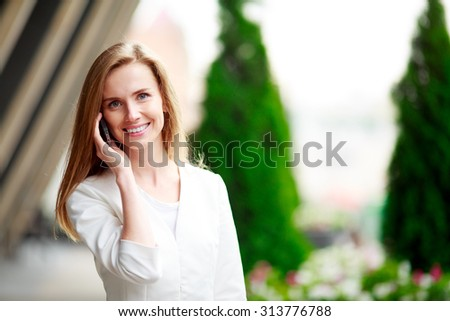 Young pretty woman with mobile phone. City defocusrd background. - stock photo