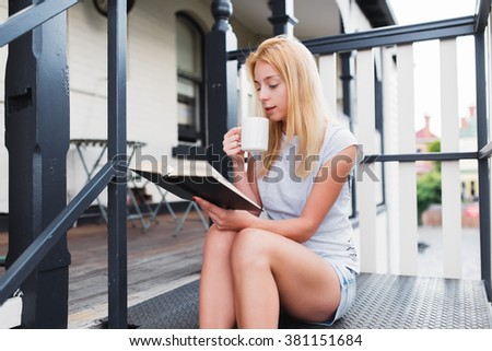 Young pretty woman with mug and book. Blonde girl is reading a  book and drinking tea or coffee