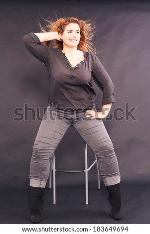 Young pretty woman with overweight sitting on a bar stool in denim shirt and jeans, with fluttering hair, studio shot / Young pretty woman with overweight sitting on a bar stool - stock photo