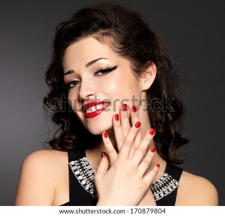 Young pretty woman with red manicure and  lips.  Fashion model with bright positive emotions - stock photo