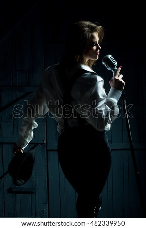 young pretty woman with sexy stylish cloth singing into silver studio microphone in retro hat braces and pants in darkness