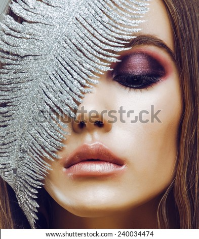 young pretty woman with silver feather like ice decoration to new year, face close up, weathered lips - stock photo
