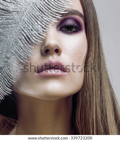 young pretty woman with silver feather like ice decoration to new year, face close up, weathered lips, winter coming