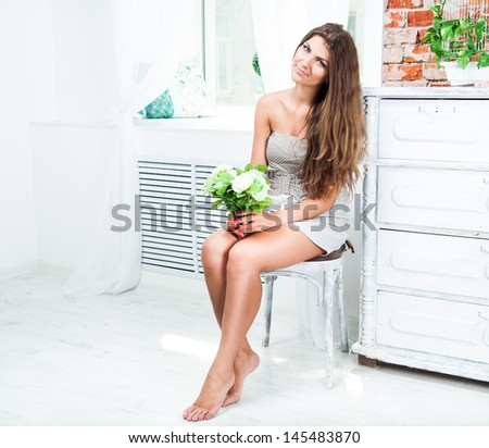 Young pretty woman with the flowers in beautiful interior - stock photo