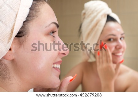 Young pretty woman with towel on head applying cream on face in front of mirror in bathroom. Beauty and skin care concept - stock photo