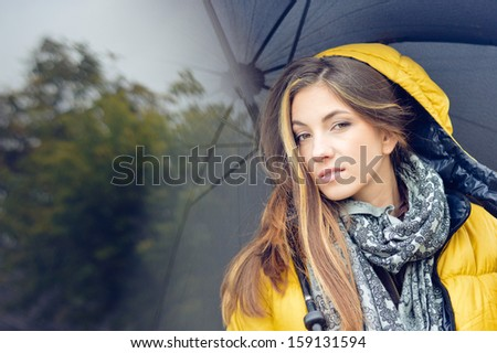 Young pretty woman with umbrella wearing warm yellow coat looking at camera on spring or autumn outdoors background - stock photo