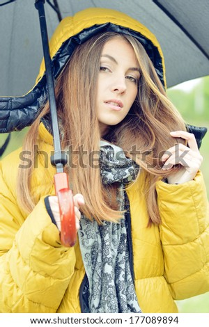 Young pretty woman with umbrella wearing warm yellow coat outdoors - stock photo