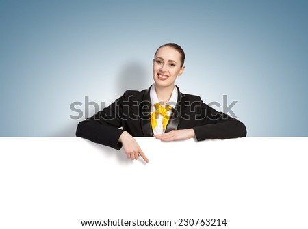 Young pretty woman with white blank banner on color background - stock photo
