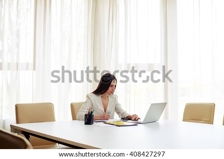 Young pretty woman working on her laptop and writing some data in a pad  in white modern office