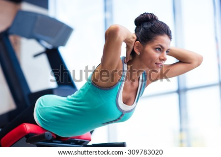 Young pretty woman workout on exercises machine in fitness gym - stock photo