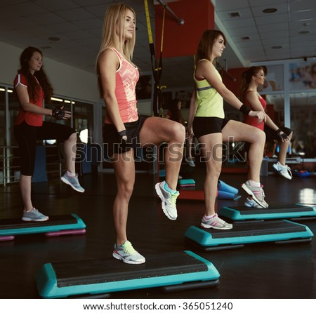 Young pretty women exercising on step boards in aerobics class. Fitness people working out with steppers in the gym.  - stock photo