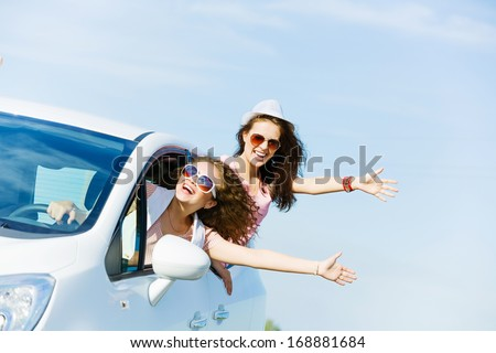 Young pretty women leaning out of car window - stock photo