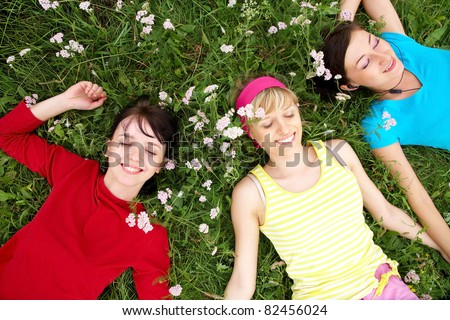 Young pretty women resting on the green grass in summer